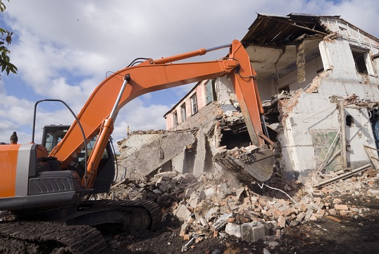Demolition of old house with excavator