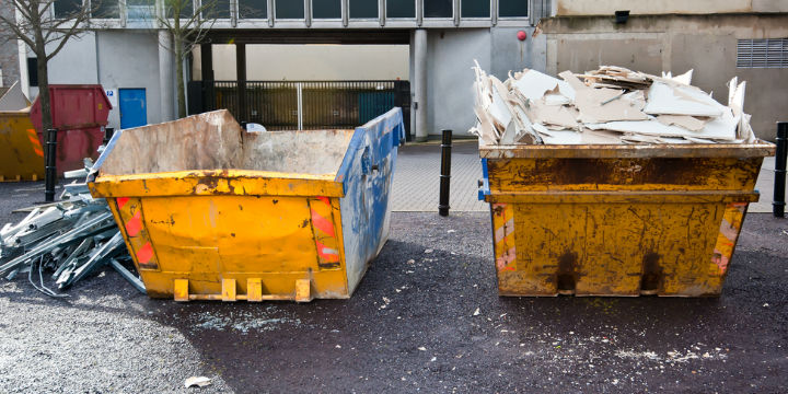 Two skips in front of commercial building