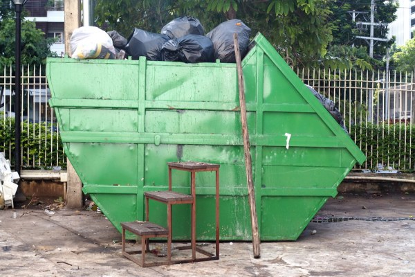 Side view of a green skip bin filled with rubbish bags