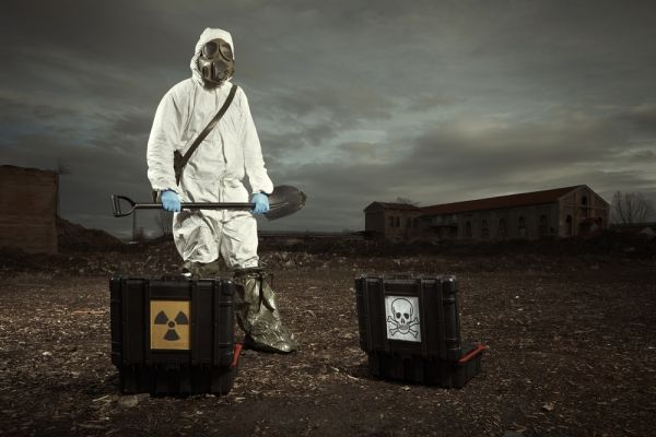 Person in hazmat gear and gas mask with a shovel