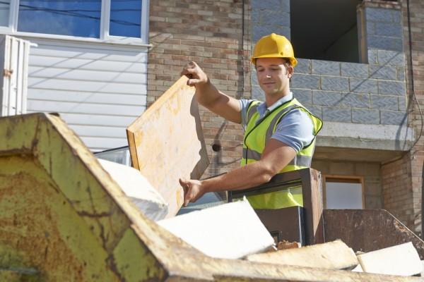 Builder putting timber waste into skip bin hire